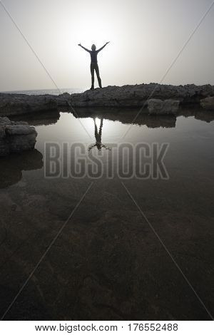 Woman with outstretched hands situated in rock between sea and puddle. Dusk.