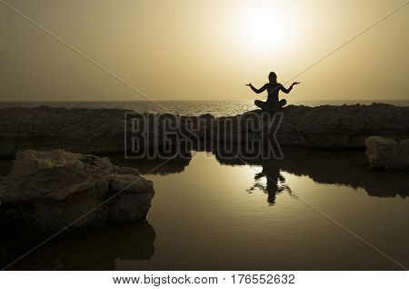 Yogi silhouette against beautiful sunset over sea background. Foreground - woman and gold sky reflections in water.