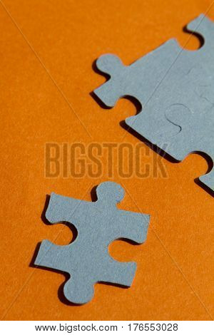 Jigsaw puzzle pieces on bright orange background vertical view