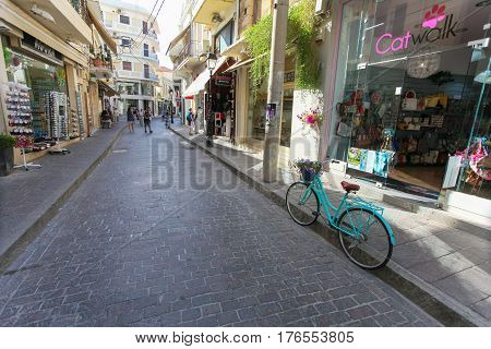 Rethymno Island Crete Greece - June 23 2016: Green colored bicycle with basket with purple flowers is parked on the narrow street of Rethymnon (part of Old Town) where there are a lot of small cafes and shops