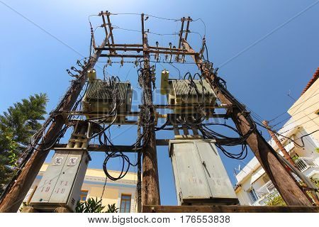 Rethymnon Island Crete Greece - June 23 2016: High voltage power pole with with a lot of wires and some transformators on the street of part Old Town in Rethymnon.