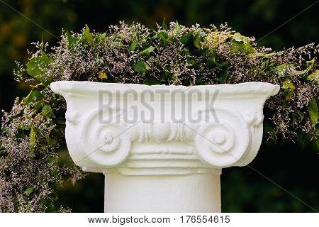 Beautiful flower garland on stone pedestal, closeup