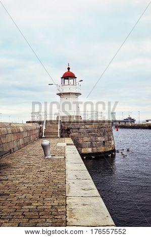 Old Lighthouse in harbor Malmo Sweden. Spring season.