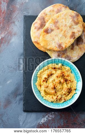 Hummus chickpeas with spices and pita flat cake in a plate on a background of gray stone. Selective focus.
