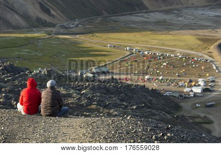 Camping tents in a mountain valley and two tourist on the rock in the foreground