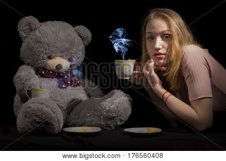 Tea time for young girl with big teddy on black background