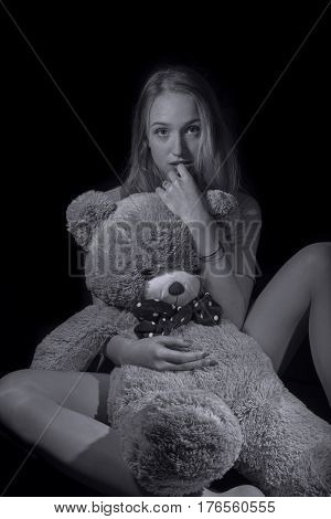 Young girl with big teddy on black background, B&W