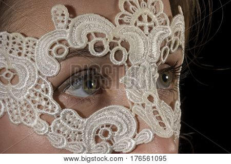 Teenage girl wearing lace mask on black background