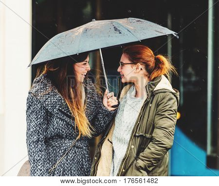 Two 20-25 year old girls under the rain, wearing warm jackets, early spring weather
