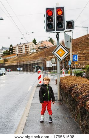 Little boy playing outdoors in early spring, walking next to road, wearing black waterproof jacket, red trousers and rain boots. Image taken in Lausanne, Switzerland