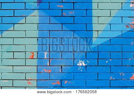 Old colorful (blue) paint with cracks on brick wall as background texture