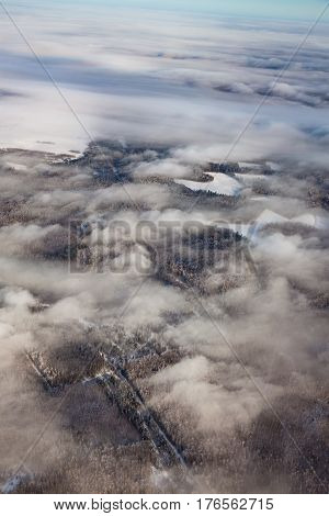 Aerial view of forest plain in Nizhny Novgorod Region during a winter day. Light low clouds are flying over trees and fields.