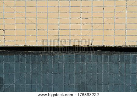 Mosaic tiles on the facade of a house. Architectural background made of beige and black mosaic wall