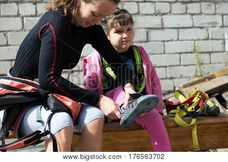 Family of mother and daughter wearing climbing shoes preparing for climb the wall