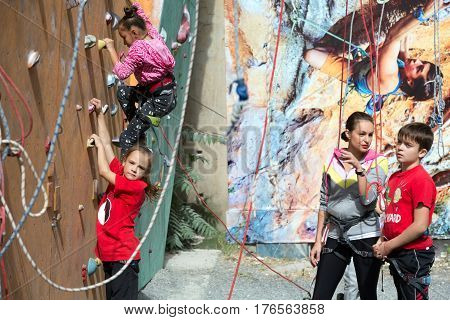 Little participants of climbing competitions warming up and trying holds of climbing wall. Family Climbing Competitions Mother, Father and Me , Dnipro, Ukraine, September 18, 2016
