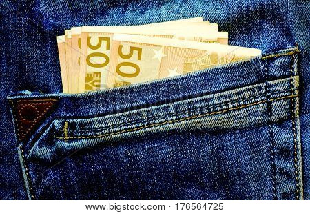 Money on the pocket in the blue jeans