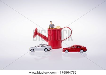 Figurine Standing In A Watering Can With Cars Beside
