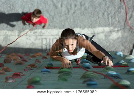 Female Climber in white shirt with serious face and her Son below starting his try on rock climbing wall