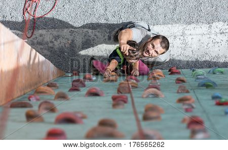 Father teaching his little baby daughter rock climbing at artificial climbing wall top view