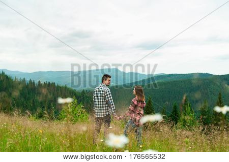 Loving couple having fun on summer vacation. Portrait of a happy couple laughing. Summer holidays love relationship concept - smiling couple in mountaines. Couple outdoors