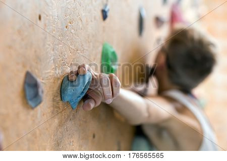 Young Female Climber in glasses on wall of indoor climbing gym with focus on hand holding the hold face is blurred and unrecognisable
