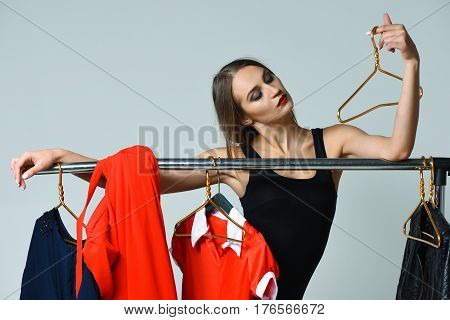 Pretty girl or sexy woman slim fashion model with sexi red lips in black bodysuit posing with hanger at clothes rack wardrobe colorful clothing dresses on grey background