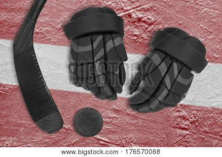 Hockey puck stick gloves and the image of the Latvian flag on the ice of the sports arena