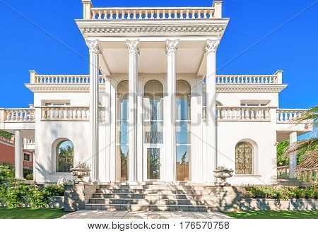 The facade of a luxurious residence with columns in the Corinthian style with large windows. Luxury house in a classic style. Beautiful exterior and front entrance.