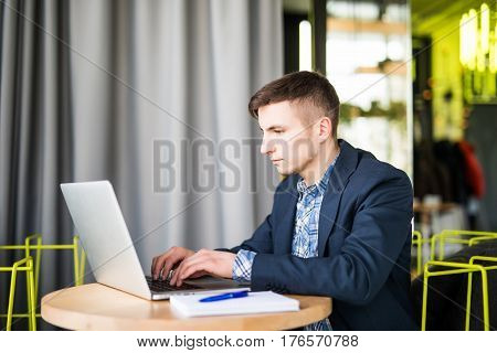 Happy Young Man Works On His Laptop To Get All His Business Done Early In The Morning With His Cup O