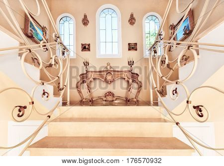 Luxurious staircase with marble steps and decorative and ornamental iron railings. On the top are decorating furniture in neoclassical style a table with candles.