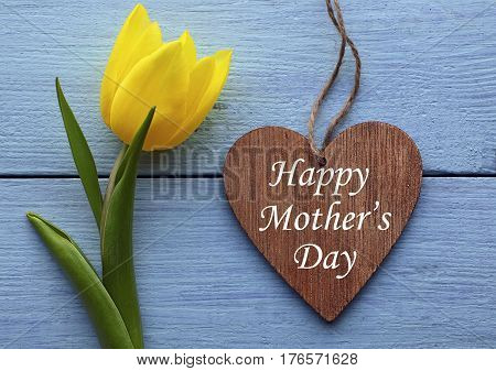 Happy Mother's Day.Yellow tulip and decorative wooden heart on blue wooden background.Mother's Day greeting card.Selective focus.