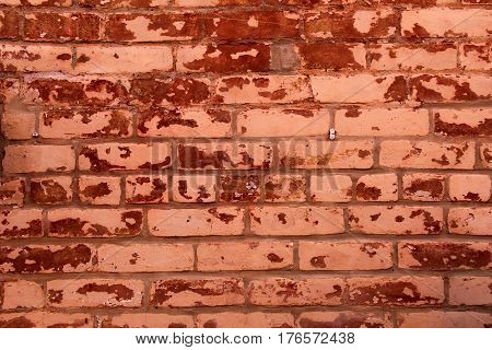 Horizontal image of old red brick wall, scarred and weathered with age.