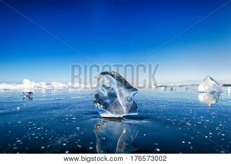 Transparent ice block at frozen surface with reflection/ Winter Baikal lake