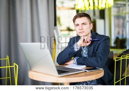 Tensed Young Man Working On Laptop At Cafe Table And Thinking