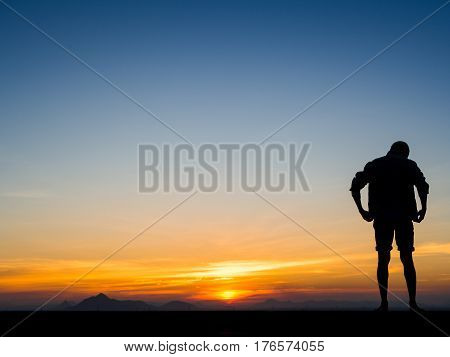 Silhouette of young man on sunset or sunrise. Confident teenage boy thinking. Hope. Sadness. Freedom.