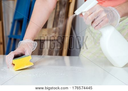 Person doing fine cleaning of white table with liquid spray and yellow wisp
