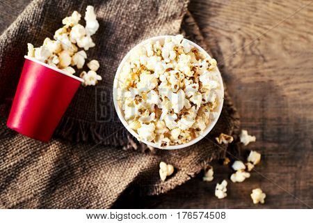 Salt popcorn in a red cardboard box on the wooden table Cinema concept