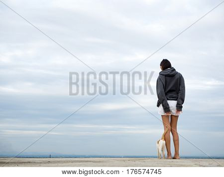 Beautiful lonely young pretty girl standing on the roof,looking away on blue sky background