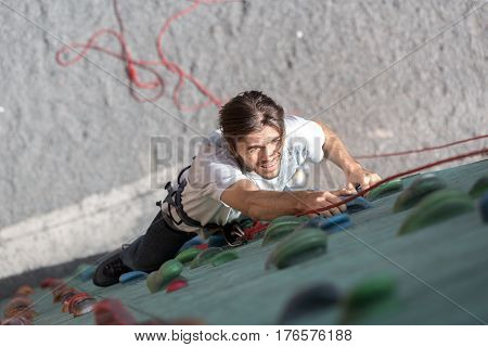 Mature Male climber trying to reach the hold on vertical wall of rock climbing competitions. Family Climbing Competitions Mother, Father and Me , Dnipro, Ukraine, September 18, 2016