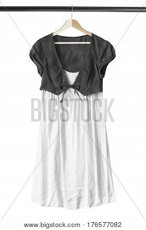 Black and white cotton dress on wooden clothes rack isolated over white