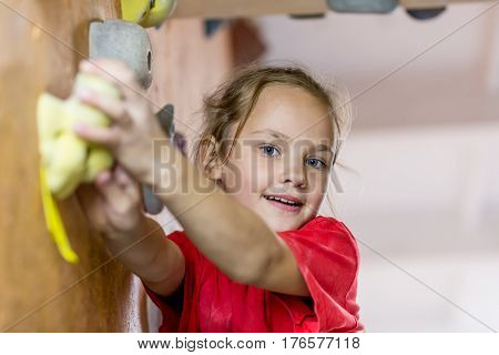 Junior Climber Girl in red shirt hanging on holds on climbing wall of indoor gym. Family Climbing Competitions Mother, Father and Me , Dnipro, Ukraine, September 18, 2016