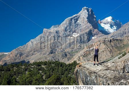 Young woman raising hands enjoying warm morning sunlight at mountains
