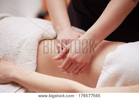 A woman receiving a belly massage at spa salon