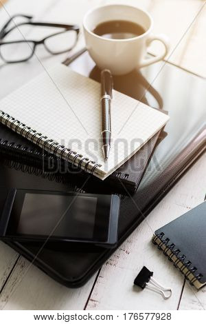 Notebook with laptop and cup of coffee on wooden desk Top view