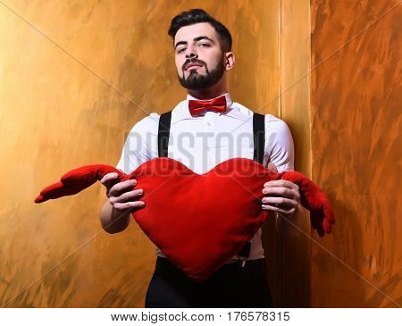 Bearded Man Holding Red Plush Heart With Serious Face