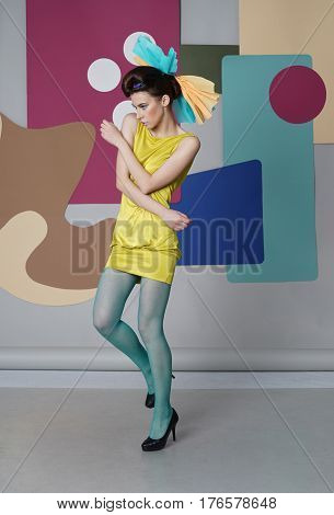 Young girl in short dress moving on the multicolor background. Fashion-story, Danish design. Eccentric outfit: short yellow dress, green tights, high heels. Backdrop: circles, rectangles, Egg chair.