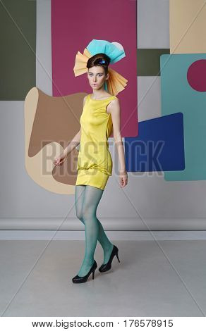 Young girl in eccentric dress dancing on the color background. Fashion-story, Danish design. She dressed in short yellow dress, green tights, high heels.