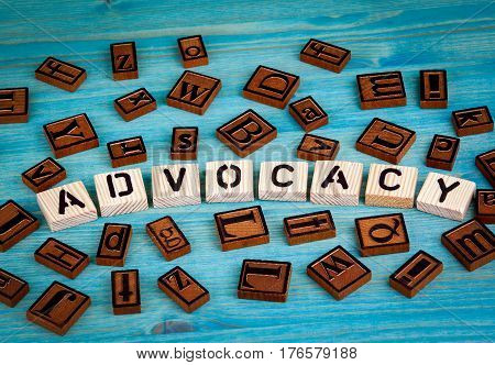 advocacy word written on wood block. Wooden alphabet on a blue background.