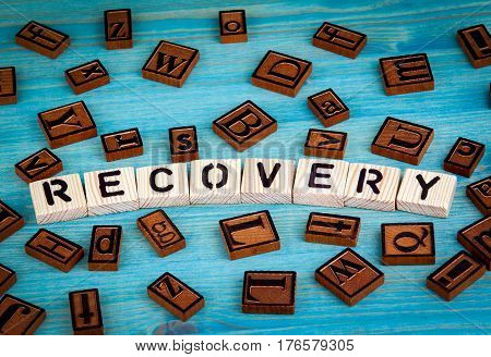 recovery word written on wood block. Wooden alphabet on a blue background.