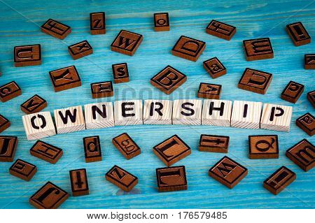 ownership word written on wood block. Wooden alphabet on a blue background.